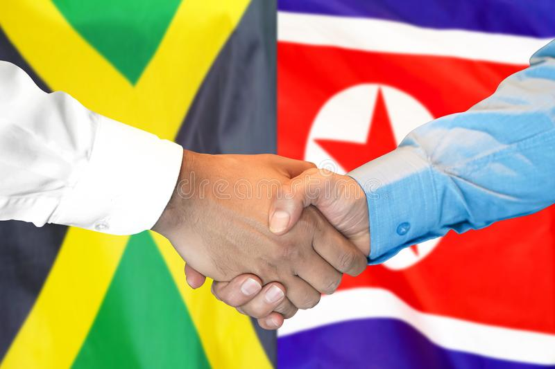 Handshake on Jamaica and North Korea flag background royalty free stock photography