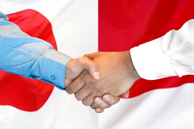 Handshake on Japan and Monaco flag background royalty free stock images