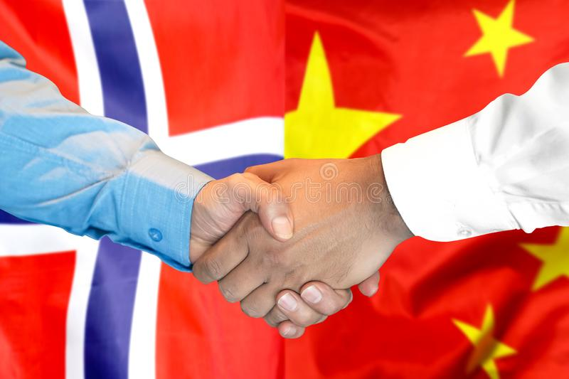 Handshake on Norway and China flag background stock images
