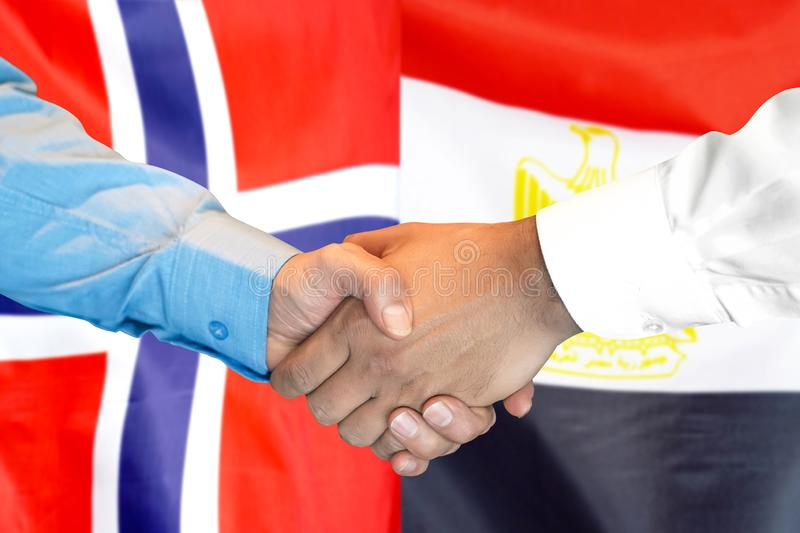 Handshake on Norway and Egypt flag background royalty free stock photos