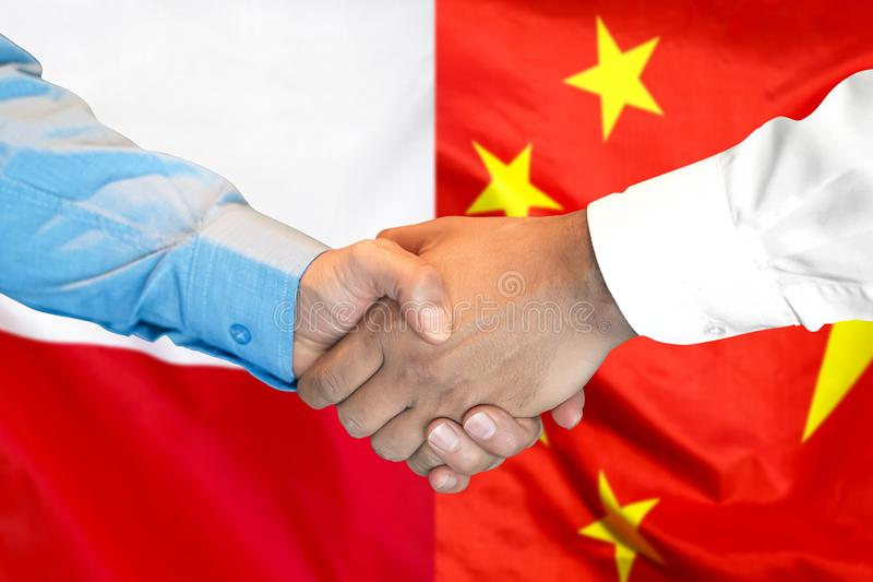 Handshake on Poland and China flag background royalty free stock photography