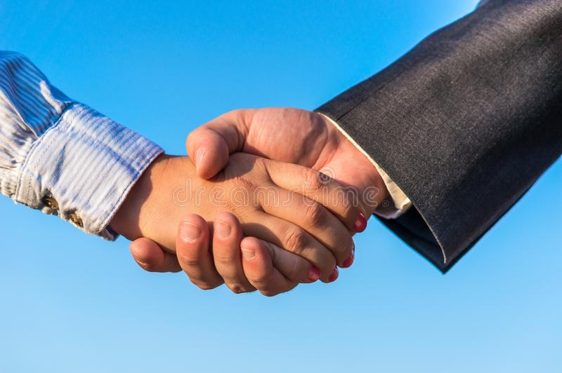 Business handshake. On the blue sky background royalty free stock photography