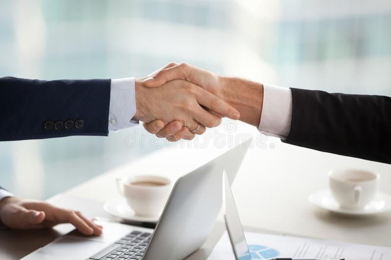 Business handshake concept, male partners businessmen in suits shake hands stock photography