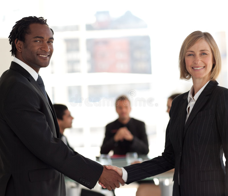 Business handshake in front of workgroup. Friendly Business handshake in front of workgroup royalty free stock photos