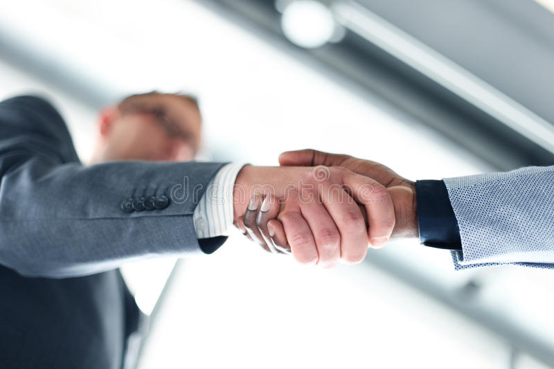 Business handshake. Business man giving a handshake to close the deal stock images