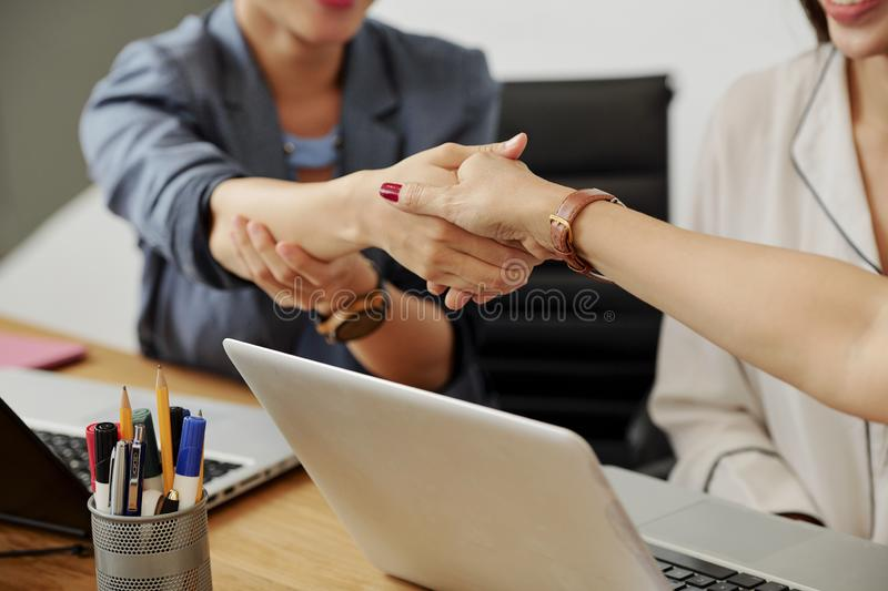 Business handshake during meeting. Close-up of two colleagues sitting at the table and shaking hands they greeting to each other or concluding a deal at meeting royalty free stock photos