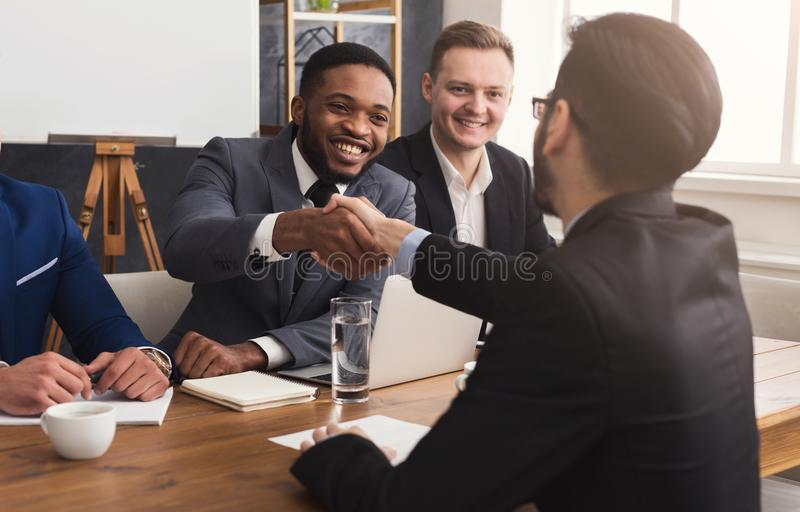 Business handshake at multiethnic office meeting royalty free stock photos