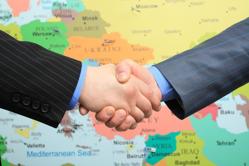 Business handshake over world map. Business handshake over colored political world map background stock photo