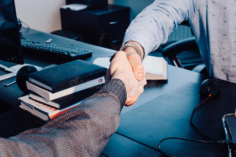 Business handshake. Business handshake and business people concept. Two men shaking hands over sunny office background. royalty free stock photo