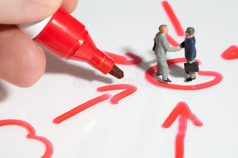 Business handshake sealing the deal. Two tiny miniature businessmen giving a business handshake sealing the deal standing in a schematic handrawn diagram stock photos