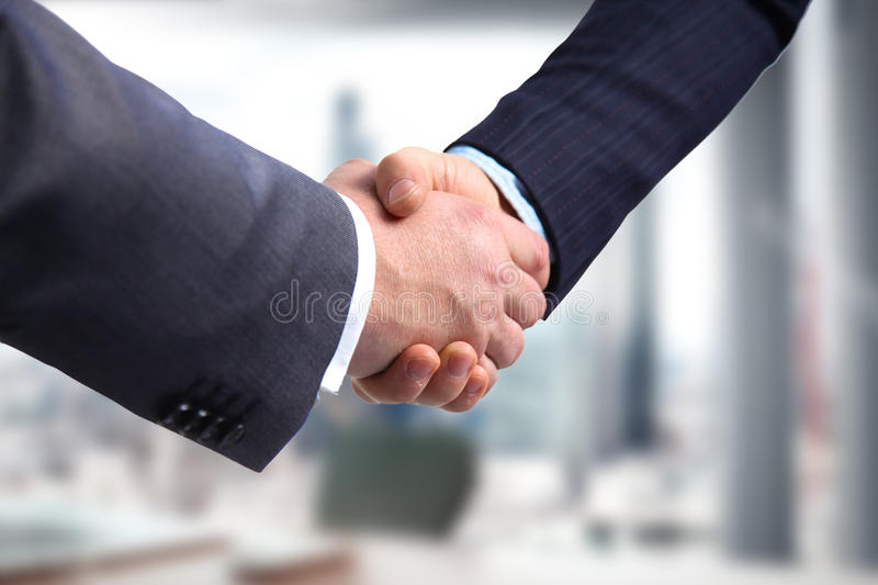 Business handshake. Two businessman shaking hands with each othe. R in the office royalty free stock photo