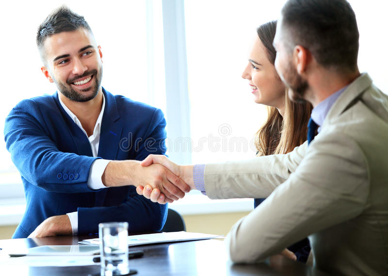 Business handshake. Handshake of two business men closing a deal at the office royalty free stock images