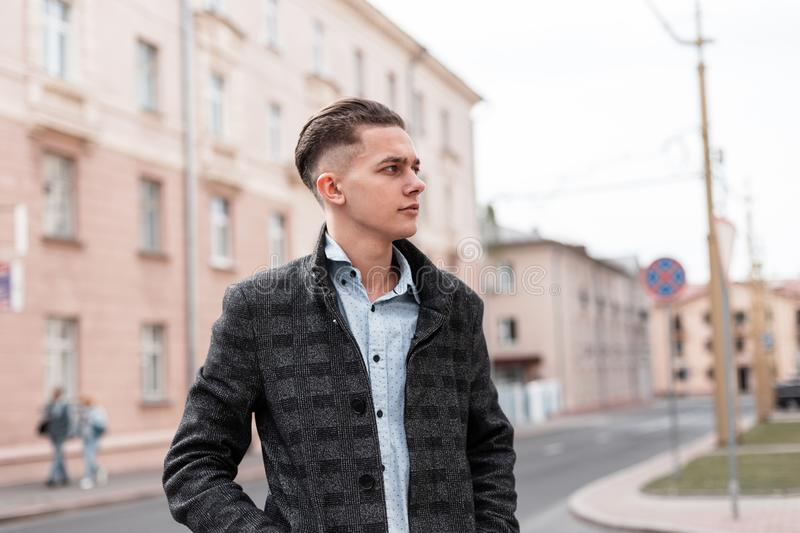 Business handsome young man with a fashionable hairstyle in a luxurious checkered jacket in an elegant shirt walks around the city. Near vintage buildings on a royalty free stock photography