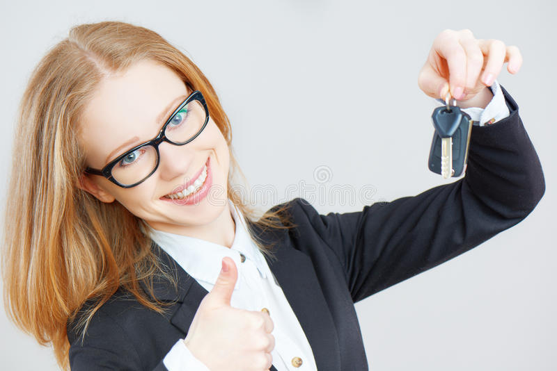 Business happy woman holding car keys. The business happy woman holding car keys royalty free stock photos