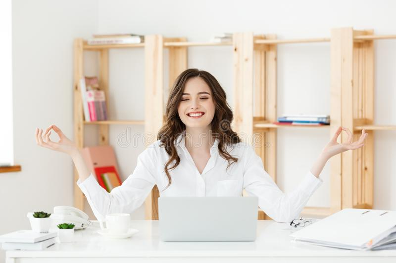 Business and Health Concept: Portrait young woman near the laptop, practicing meditation at the office desk, in front of. Laptop, online yoga classes, taking a royalty free stock photography