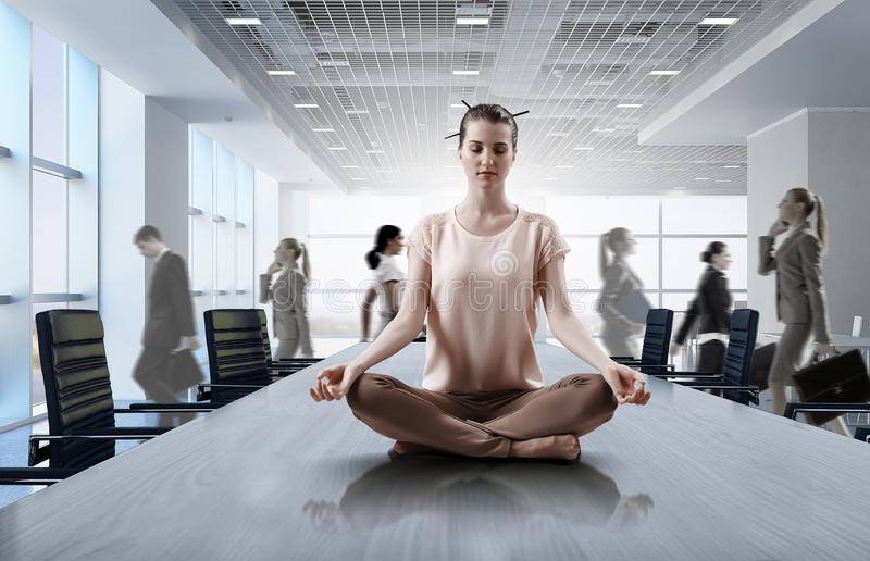 Business and healthy life balance. Mixed media. Young attractive women in office sitting on table and meditating. Mixed media stock photography
