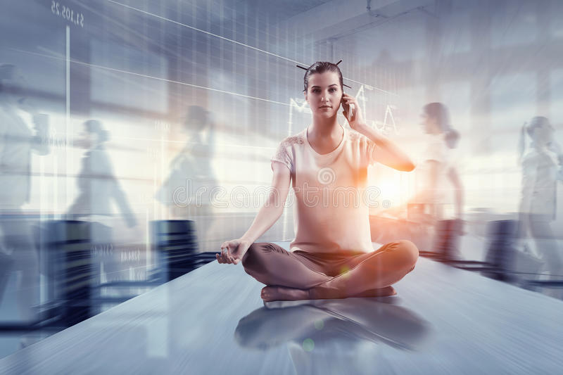 Business and healthy life balance. Mixed media. Young attractive women in office sitting on table and meditating. Mixed media stock photo