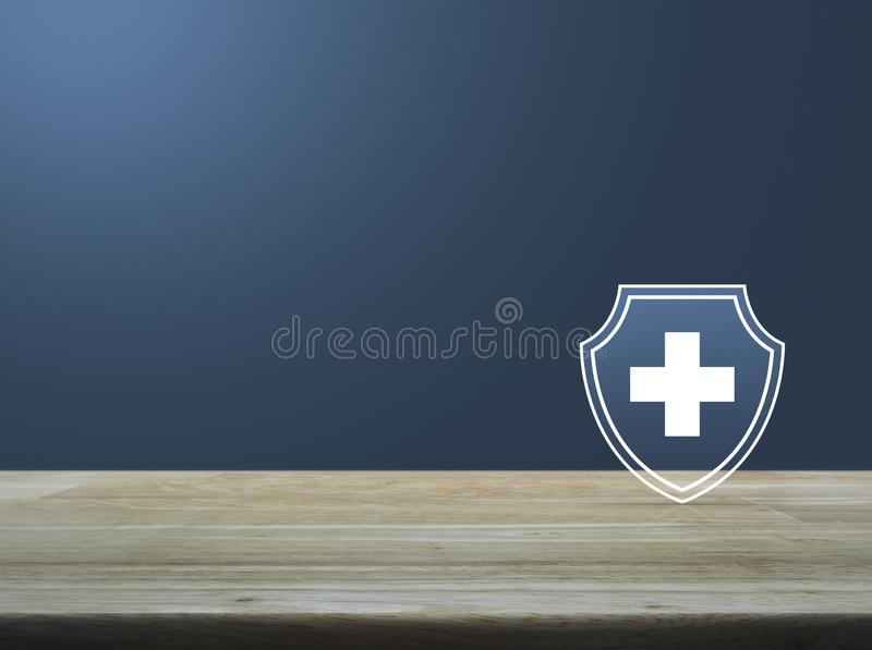 Business healthy and medical care insurance concept. Cross shape with shield flat icon on wooden table over light blue gradient background, Business healthy and royalty free illustration