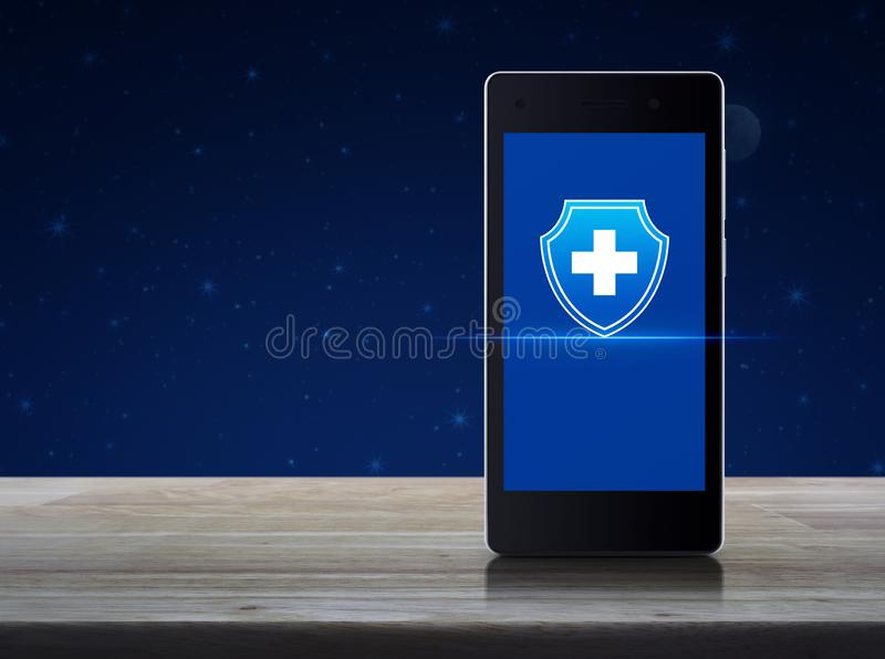 Business healthy and medical care insurance online concept. Cross shape with shield flat icon on modern smart mobile phone screen on wooden table over fantasy stock illustration