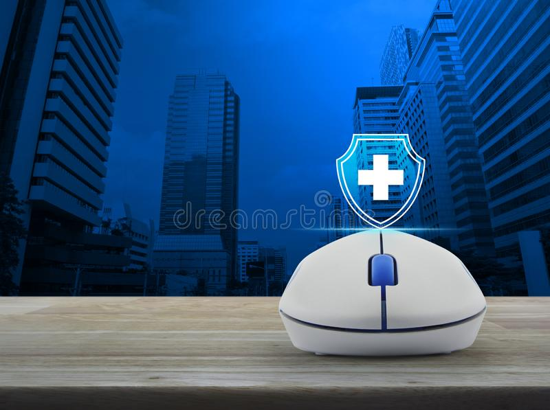 Business healthy and medical care insurance online concept. Cross shape with shield flat icon on wireless computer mouse on wooden table over modern office city vector illustration