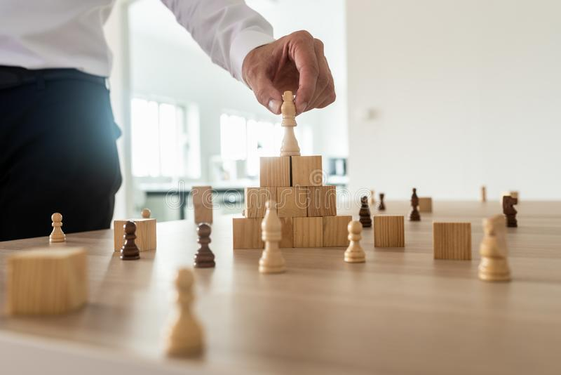 Business hierarchy concept. With businessman placing chess figure of king on top of wooden stacked wooden blocks and other figures spread on office desk royalty free stock image
