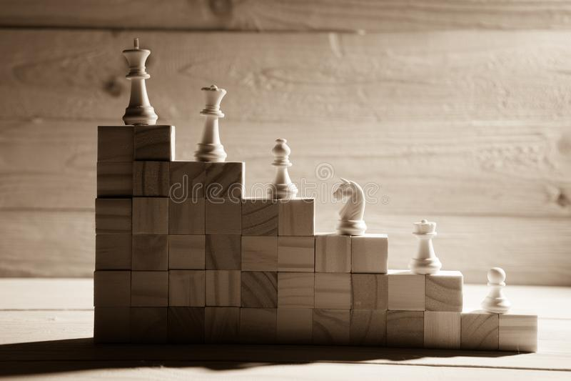 Business hierarchy. Strategy concept with chess pieces. Chess standing on a pyramid of wooden building blocks with the king at the top. copy space stock photo