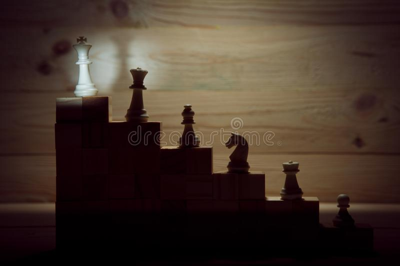 Business hierarchy. Strategy concept with chess pieces. Chess standing on a pyramid of wooden building blocks with the king at the top. copy space royalty free stock image