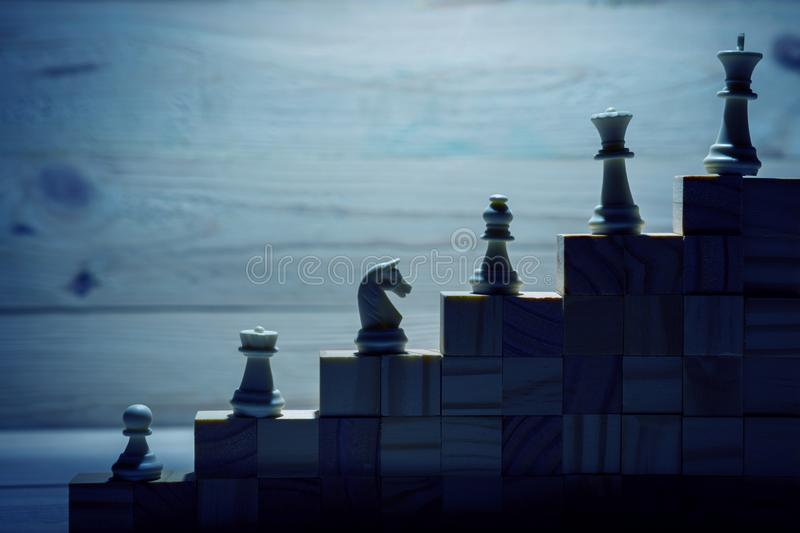 LBusiness hierarchy. Strategy concept with chess pieces. Business hierarchy. Strategy concept with chess pieces. Chess standing on a pyramid of wooden building royalty free stock photos