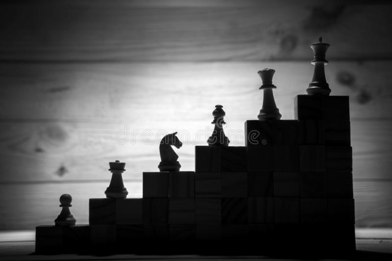 Business hierarchy. Strategy concept with chess pieces. Chess standing on a pyramid of wooden building blocks with the king at the top. copy space stock photography
