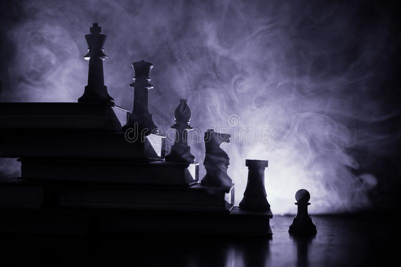Business hierarchy. Strategy concept with chess pieces. Chess standing on a pyramid of wooden building blocks with the king at the. Business hierarchy. Strategy stock photo