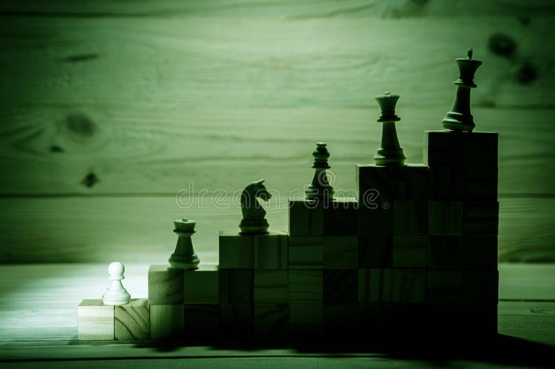 Business hierarchy. Strategy concept with chess pieces. Chess standing on a pyramid of wooden building blocks with the king at the top. copy space royalty free stock photo
