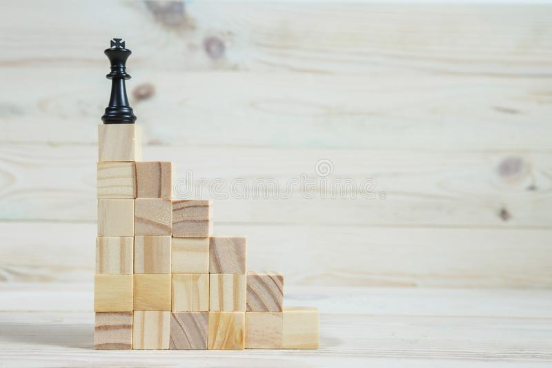 Business hierarchy. Strategy concept with chess pieces. Chess standing on a pyramid of wooden building blocks with the king at the top. copy space royalty free stock images