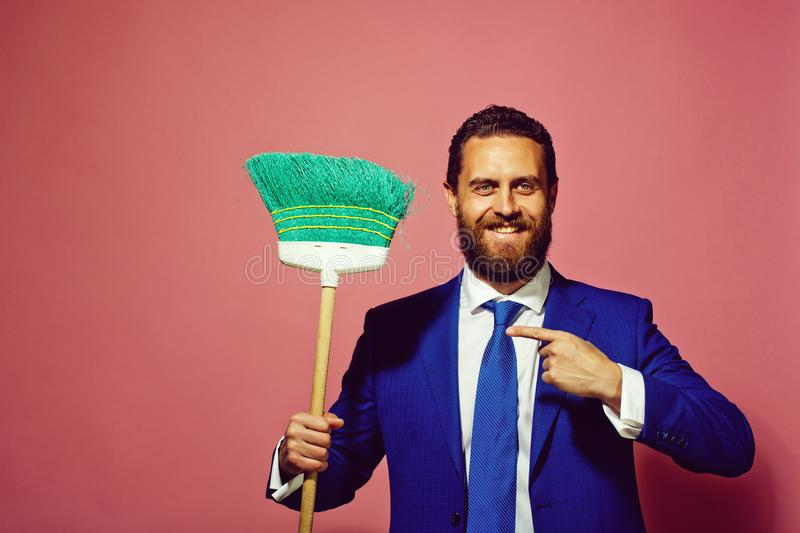 Business and home, handsome happy man or businessman with broom stock photo