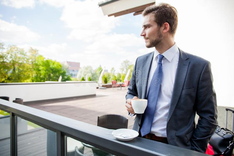 Business, hot drinks and people and concept - young serious businessman with paper coffee cup over office building. stock image