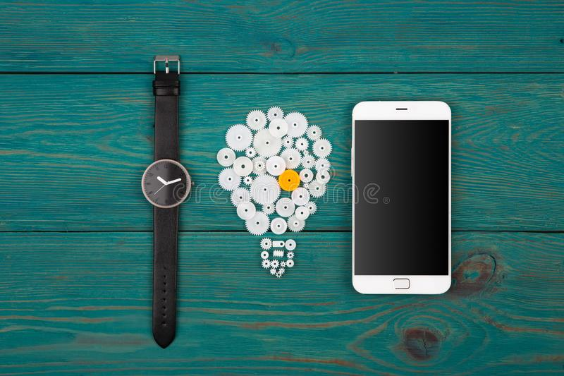Business idea concept - bulb sign and phone on the desk. Business idea concept - bulb sign, watch and phone on the desk royalty free stock photo