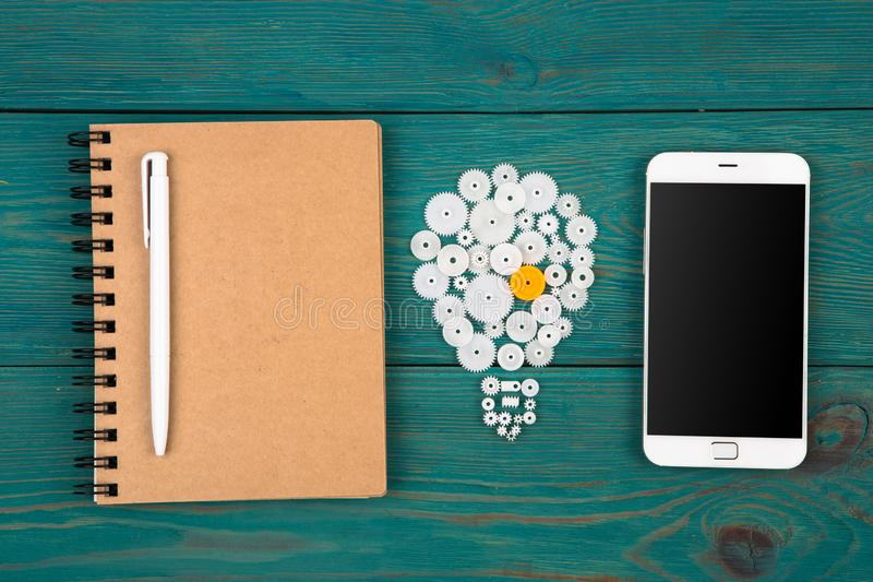 Business idea concept - bulb sign and phone on the desk. Business idea concept - bulb sign, notepad and phone on the desk royalty free stock photo