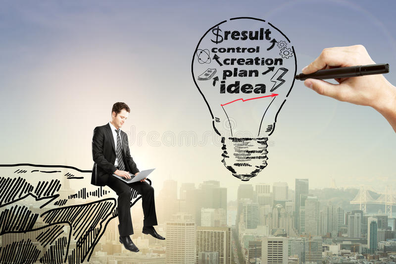 Business idea. Concept with businessman using laptop on drawn cliff and hand sketching abstract light bulb with text on city background with sunlight stock photos