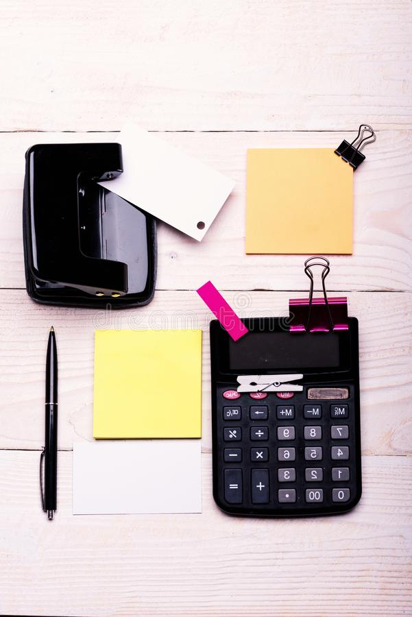 Business idea concept. Business card with empty space. And yellow sticky notes. Stationery and calculator. Bookmark of pink color near pen and hole punch on stock photography