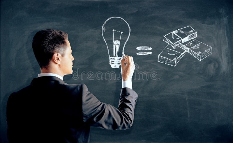 Business idea concept. Man drawing creative lamp and money sketch on chalkboard. Business idea concept royalty free stock photography