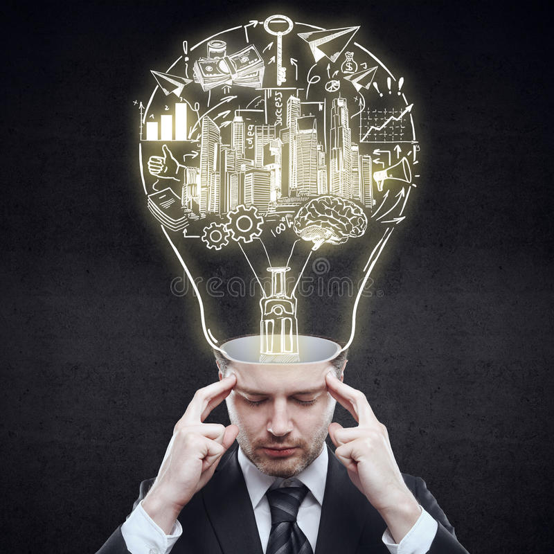 Business idea concept. Pensive businessman with abstract business sketch inside light bulb head on dark background. Idea concept royalty free stock photography