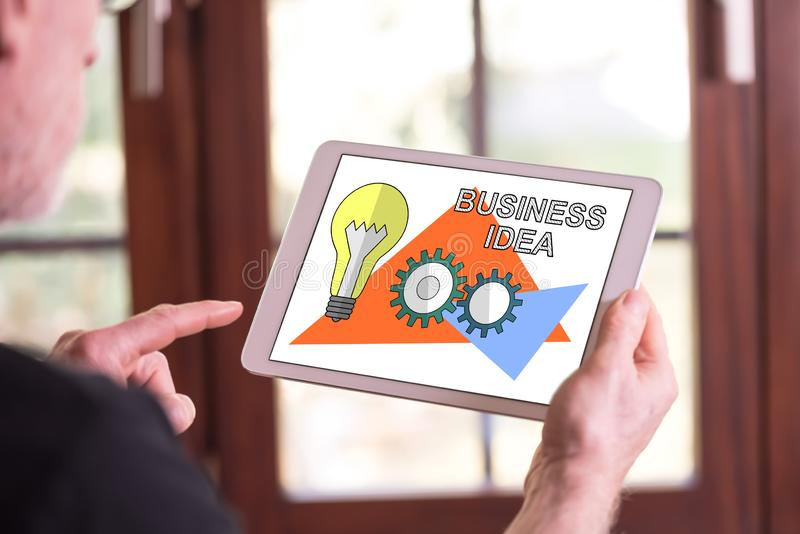Business idea concept on a tablet. Man holding a tablet showing business idea concept stock photos