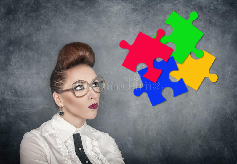 Business Idea concept. Woman looking on puzzle. On the blackboard background stock photography