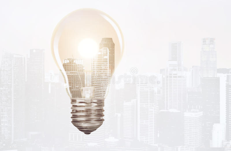 Business idea and growth concept. Business idea concept. Bulb with setting sun and charts, double exposure mixed with sunset city skyline royalty free stock photography
