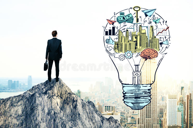 Business idea and leadership concept. Back view of young businessman standing on mountain top next to creative financial sketch inside light bulb. Business idea royalty free stock photos