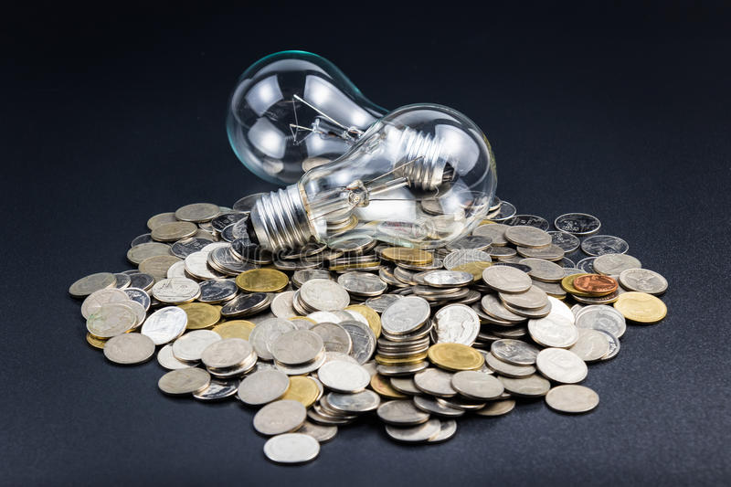 Business idea. Light bulb and pile of coins, can be used as business idea or energy saving concept stock photo