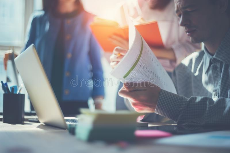Business idea report. Marketing team discussing new working plan. Laptop and paperwork in open space office royalty free stock photo