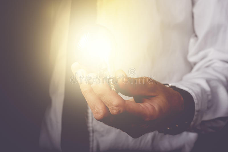 Business idea and vision. Businessman holding light bulb, concept of new ideas, innovation, invention and creativity, retro toned image, selective focus stock photography