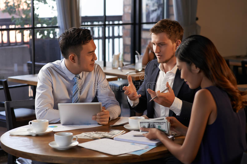 Business idea. Young men explaining business idea to coworkers, when they are sitting in cafe royalty free stock photography