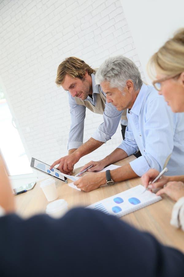 Business instructor explaining to seniors stock images