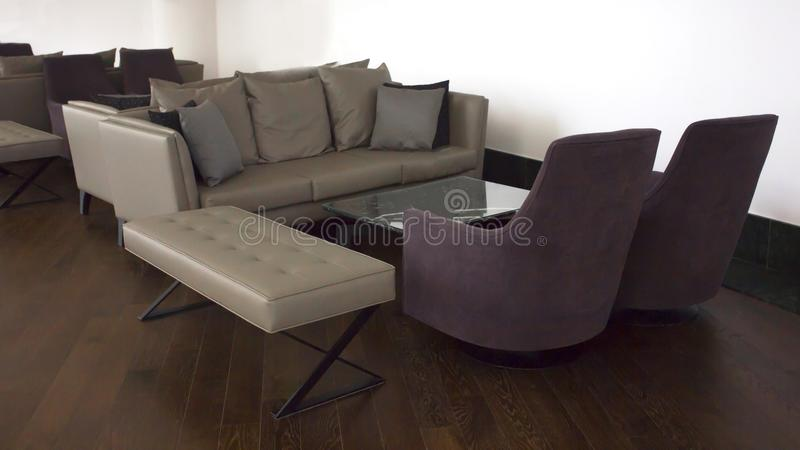 Business Interior. Brown parquet, beige leather sofas with cushions and glass table. Business Interior. Brown parquet, beige leather sofas with cushions and a stock photography